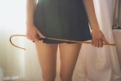 Sexy young woman with rattan school cane. Woman prepare for spanking