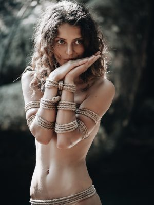 submissive woman tied in shibari looking pensive and lonely