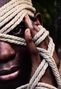 man peeking through ropes