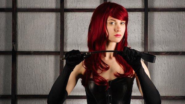beautiful redhead dominatrix holding riding crop