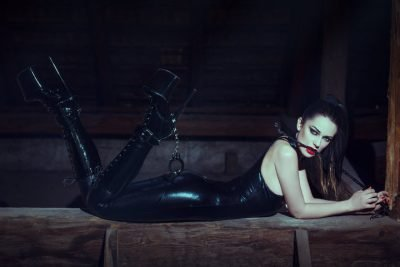 Sexy young woman with whip in mouth at night