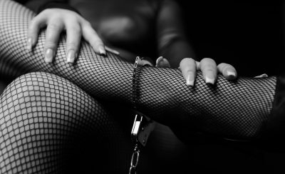 woman leg wearing fishnet hosiery and handcuffs.