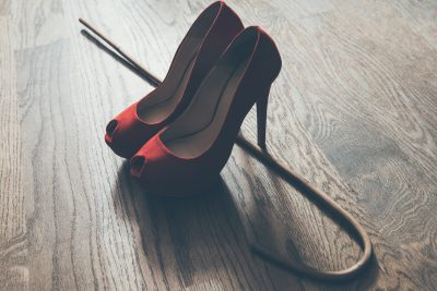 Red high heels and school cane on wooden background