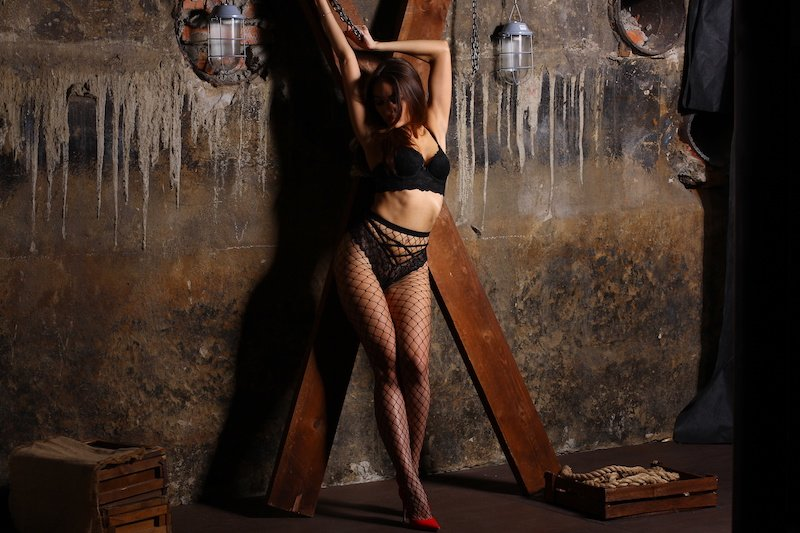 submissive girl on a st andrews cross at a BDSM play party