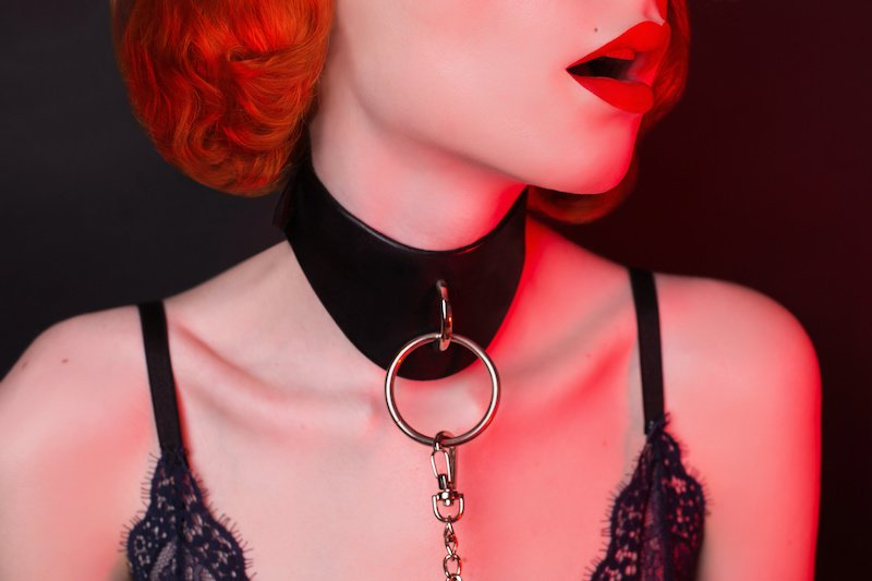 Submissive woman with collar and red lips