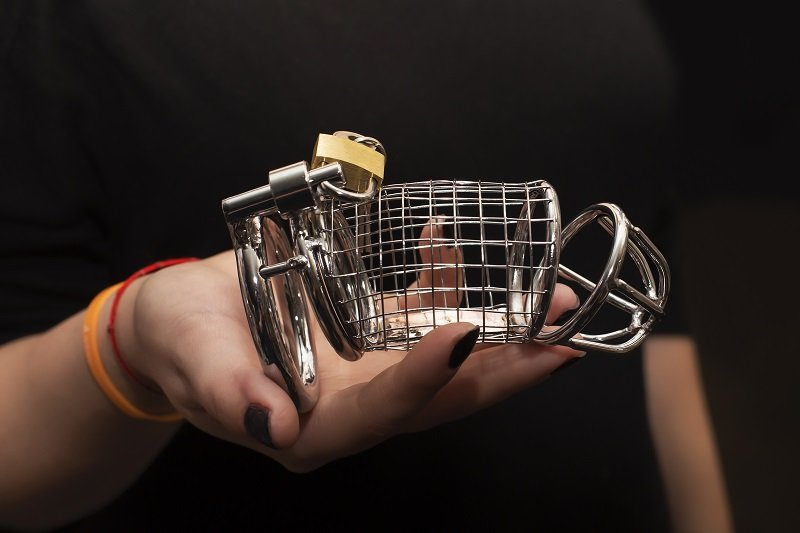 Domme holding cock cage